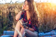 女孩坐在领域衬衣的,放松本质上,美丽的深色的头发的麦子 想法笔记薄作梦 A 免版税库存图片
