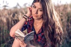 女孩坐在领域衬衣的,放松本质上,美丽的深色的头发的麦子 读想法的笔记薄 一名学生 库存照片