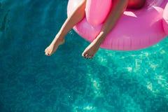 女孩坐在水池的可膨胀的床垫火鸟 免版税图库摄影