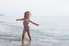 女孩坐在水的边缘 免版税图库摄影
