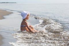 女孩坐在水的边缘 免版税库存照片