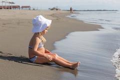 女孩坐在水的边缘 图库摄影