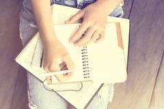 女孩坐地板和在日志写了 库存图片