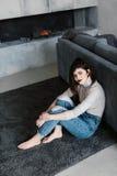 女孩坐地板在长沙发附近 女孩坐倾斜在沙发 一个舒适房子 女孩 免版税图库摄影