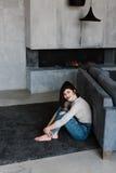 女孩坐地板在长沙发附近 女孩坐倾斜在沙发 一个舒适房子 女孩 免版税库存照片