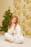 女孩坐地毯,看照相机和微笑 库存图片