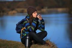 女孩坐地面和饮料茶在远足以后 图库摄影