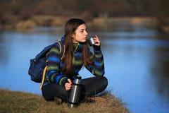 女孩坐地面和饮料茶在远足以后 免版税库存照片