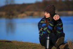 女孩坐地面和饮料茶在远足以后 库存照片