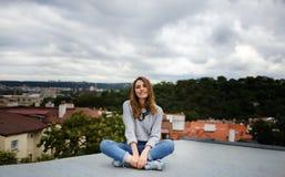 女孩坐城市的屋顶并且停放背景 免版税库存图片