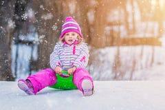 女孩坐塑料雪撬 库存图片