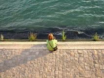 女孩坐塞纳河的银行在巴黎 免版税库存照片