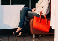 女孩坐夏天咖啡馆沙发与的在毛线衣牛仔裤和运动鞋的大红色超级时兴的提包在一个温暖的夏天 图库摄影