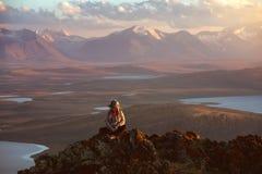 女孩坐大岩石反对山和湖 免版税库存照片