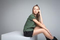 女孩坐大立方体 免版税库存图片