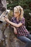 女孩坐大老树桩 库存照片