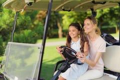 女孩坐妇女的膝部 同时他们控制一辆高尔夫车 库存照片