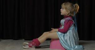 女孩坐容易和看着电视 免版税库存图片