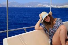 女孩坐小船在海中间 免版税库存照片