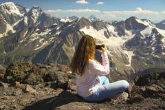 女孩坐山的上面并且拍照片 库存图片