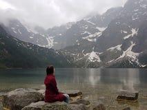 女孩坐岩石临近山的湖 免版税图库摄影