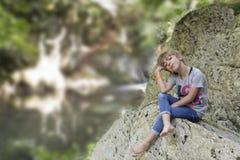 女孩坐岩石在瀑布旁边 图库摄影