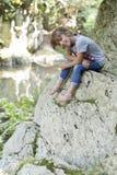女孩坐岩石在瀑布旁边 免版税库存图片