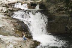 女孩坐岩石在瀑布旁边 免版税库存照片