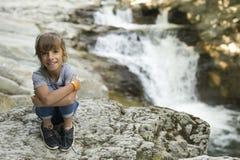 女孩坐岩石在瀑布旁边 库存照片