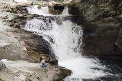 女孩坐岩石在瀑布旁边 库存图片