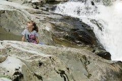 女孩坐岩石在瀑布旁边 免版税图库摄影