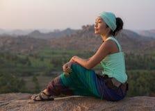 女孩坐岩石并且敬佩石风景在日落 库存照片