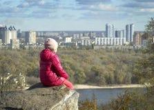 女孩坐岩石并且敬佩都市风景 免版税图库摄影