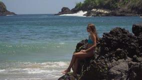 女孩坐岩石并且看海 巴厘岛印度尼西亚 股票录像