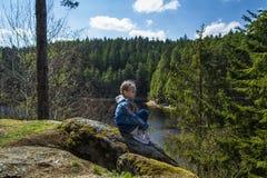 女孩坐峭壁和神色在自然,坐岩石和享受谷视图的女孩 免版税库存照片