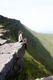 女孩坐峭壁的上面 免版税库存图片