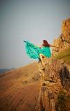 女孩坐峭壁的悬崖。 免版税库存照片
