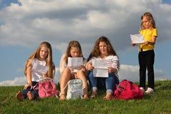 女孩坐并且读和小女孩立场近 免版税库存照片