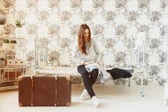 女孩坐床并且收集衣裳入手提箱 免版税库存照片