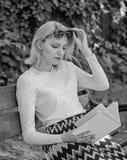 女孩坐放松与书,绿色自然背景的长凳 作为爱好的读书文学 女孩敏锐对书继续读 免版税图库摄影