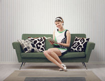 女孩坐长沙发 图库摄影