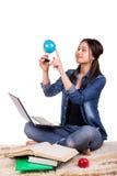 女孩坐有地球、膝上型计算机和书的地毯 免版税库存图片