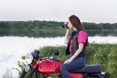 女孩坐有照相机的葡萄酒摩托车 免版税图库摄影