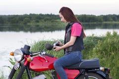 女孩坐有照相机的葡萄酒摩托车 库存照片