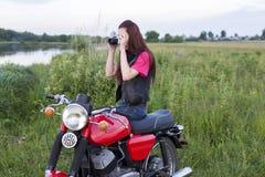 女孩坐有照相机的葡萄酒摩托车 免版税库存图片