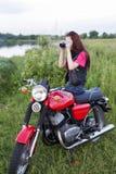 女孩坐有照相机的葡萄酒摩托车 免版税库存照片