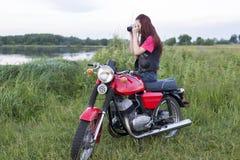 女孩坐有照相机的葡萄酒摩托车 库存图片