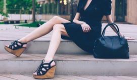 女孩坐有的台阶在一只礼服和高楔子凉鞋的大黑超级时兴的提包在一个温暖的夏天晚上 免版税库存图片