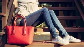 女孩坐有的台阶在毛线衣牛仔裤和运动鞋的大红色超级时兴的提包在一个温暖的夏天晚上 战争 免版税库存照片