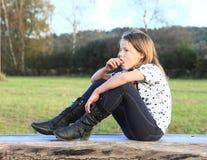 女孩坐木头 免版税图库摄影